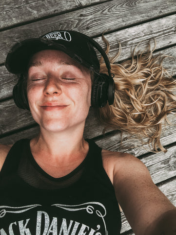 megan lies on the deck with a smile on her face, wearing a ball cap and big headphones, sweaty and red after a run