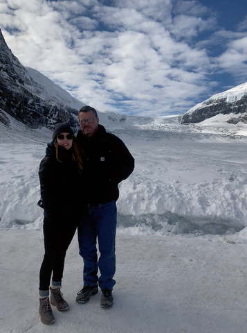 a photo of megan and her dad in coats and hiking boots. in the background - snow and mountains at the athabasca glacier, alberta