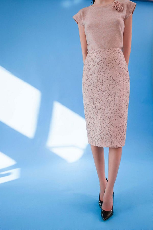 Front view of laser cut faux leather pencil skirt in blush pink colour with midi length