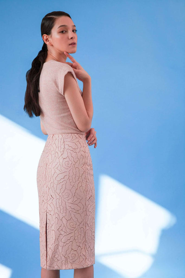 Back view of laser cut faux leather pencil skirt in blush pink colour with midi length