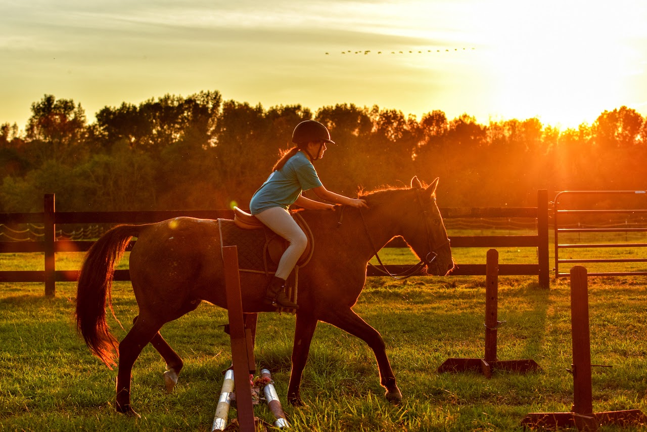 girl riding horse with sunset in background