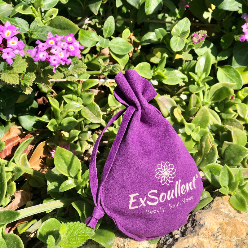 A ExSoullent Branded Flannel bag with yoni eggs inside and lush greens surrounding it