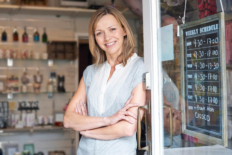 young woman outside of a small business smiling
