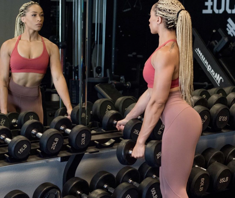 Stormi looking in mirror at weight rack