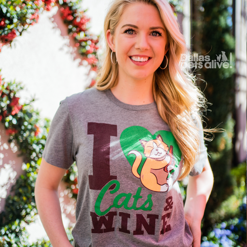 smiling female wearing grey Dallas Pets Alive! short-sleeve t-shirt with I HEART CATS & WINE printed on it