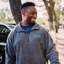 Load image into Gallery viewer, smiling male wearing grey half zip fleece embroidered with Dallas Pets Alive! logo