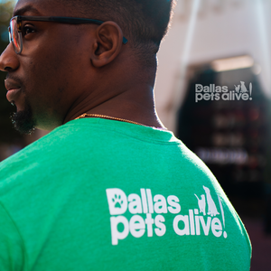 smiling male wearing green, short-sleeve t-shirt with Dallas Pets Alive! logo on the back