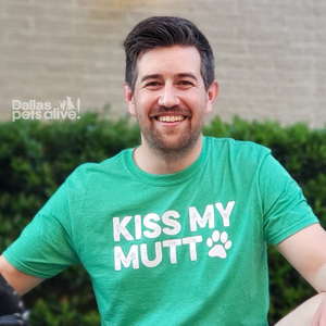 smiling male wearing Dallas Pets Alive! green, short-sleeve t-shirt with Kiss My Mutt printed on the front