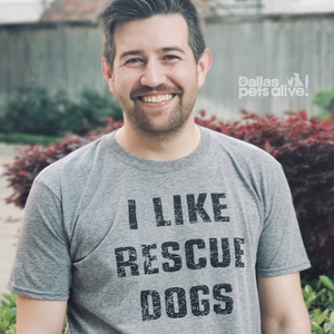 smiling male wearing grey short-sleeved t-shirt with I LIKE RESCUE DOGS printed on front