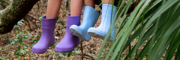 Kids Cirrus Charley Rain Boots in Bonnie Blue and Paisley Purple on figure sitting on a branch in the woods