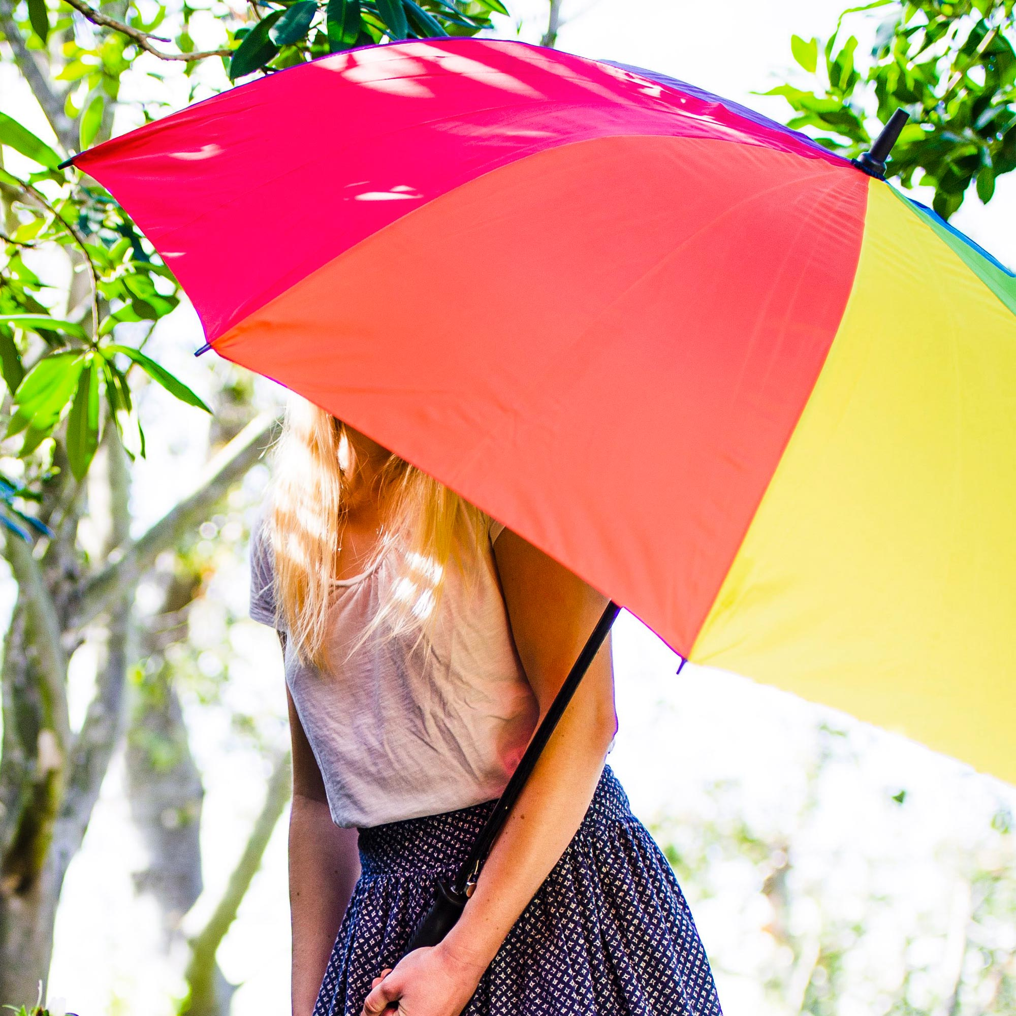 Female model holding rainbow golf umbrella over her face to protect her from the sun