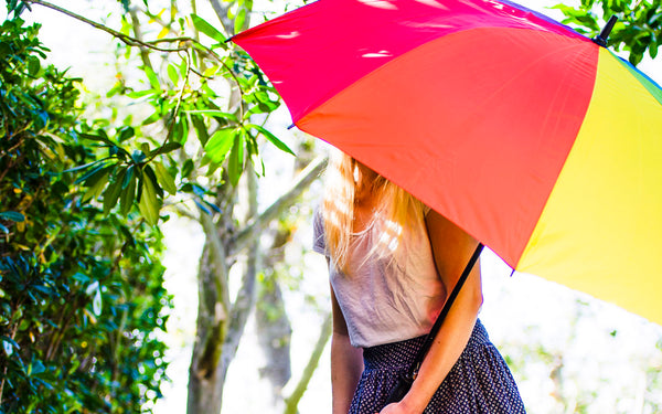 Model holding Sunguard Stick Umbrella in Rainbow on a sunny day
