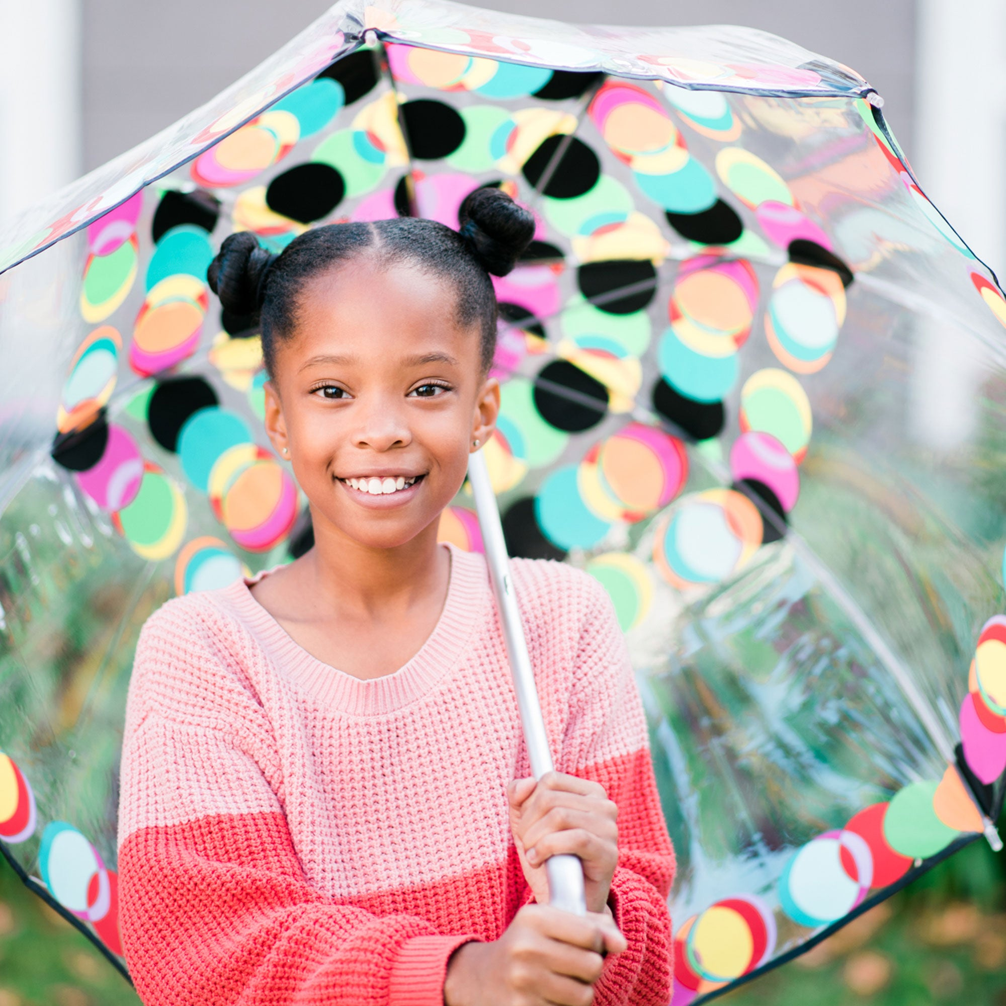 Child female model holding circle mania bubble umbrella with a big smile on her face
