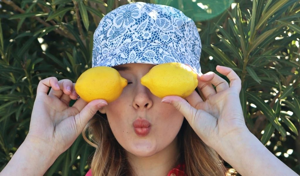 A woman in a bucket hat holding lemons in front of her eyes