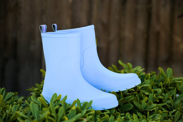 Cirrus Kids Charley Rain Boots in Bonnie Blue in front of a barn in the bushes