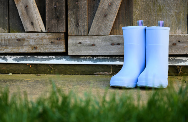 Kids Cirrus Charley Boots in Bonnie Blue in front of a barn with grass