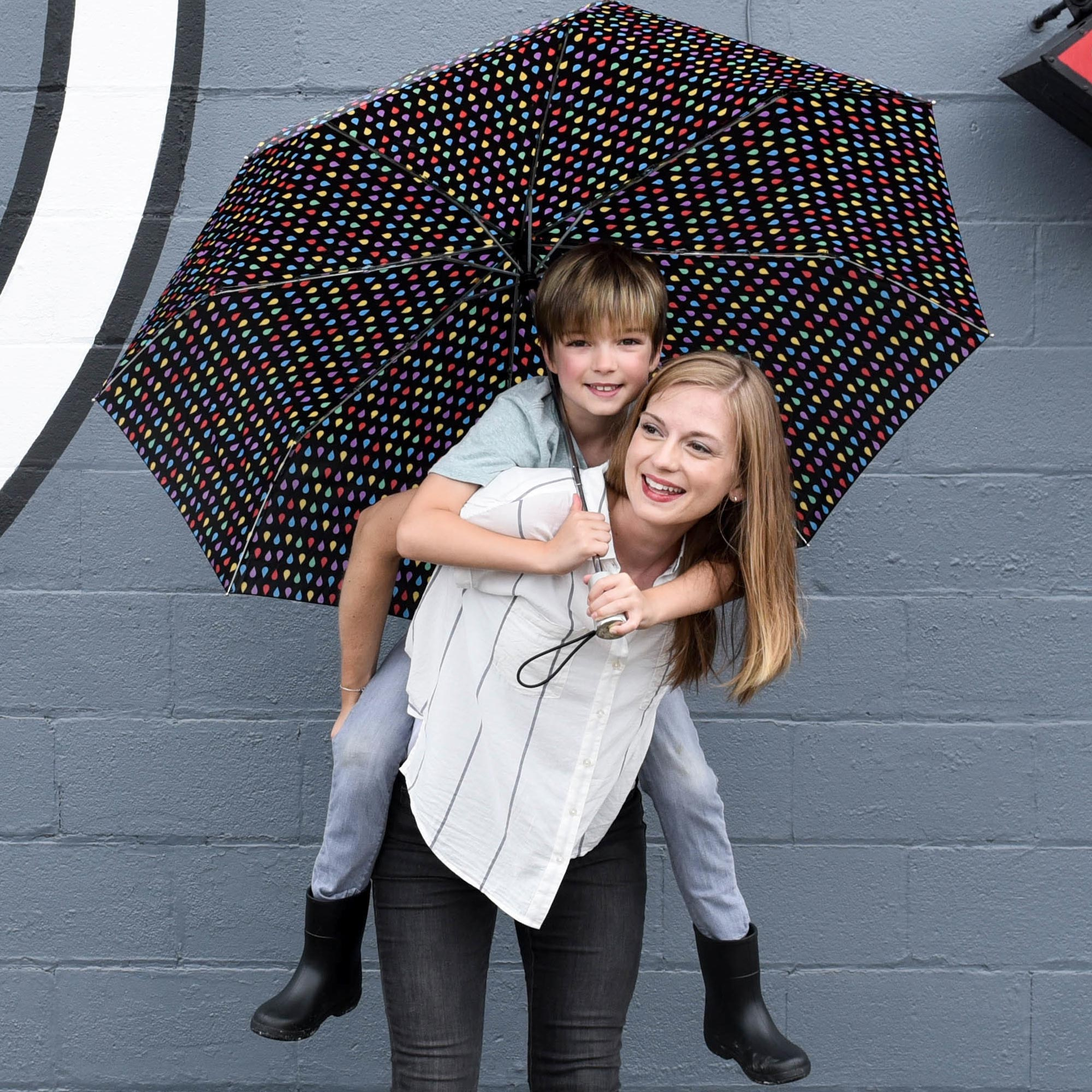 son riding on mother's back holding the mini compact umbrella with sunguard. Both laughing and smiling