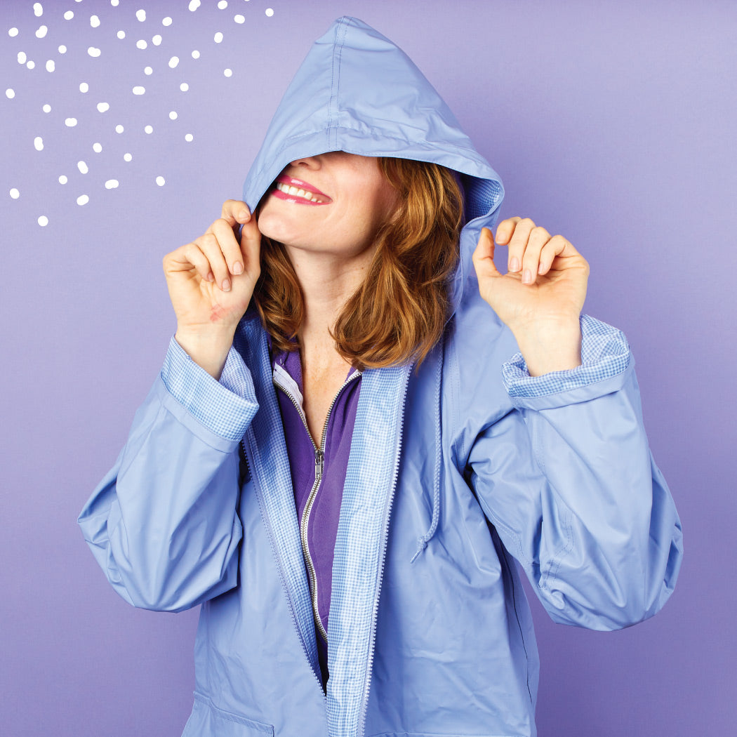 female model wearing lined rain slicker in lavender with the hood over her eyes standing in front of a purple background