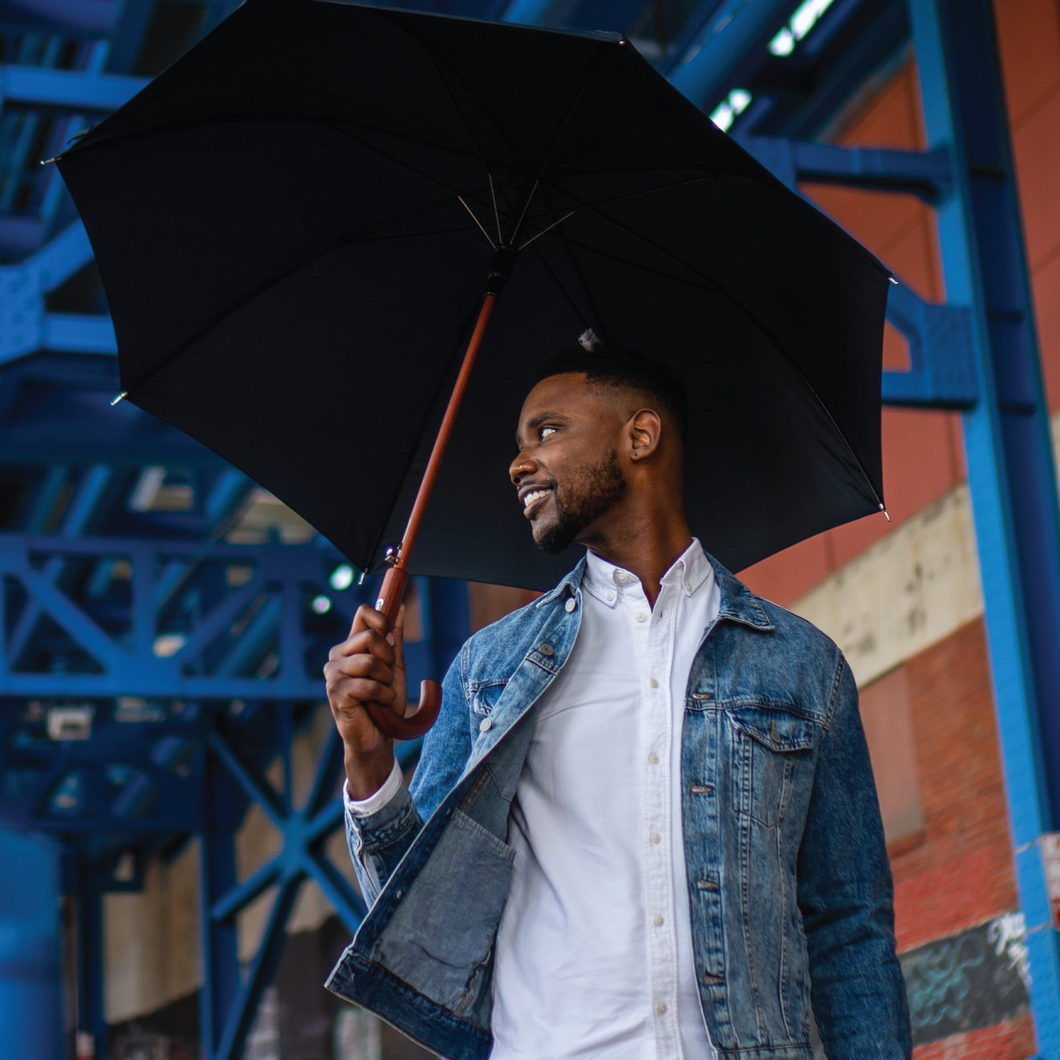 Male model holding a stick umbrella over his head under city scaffolding