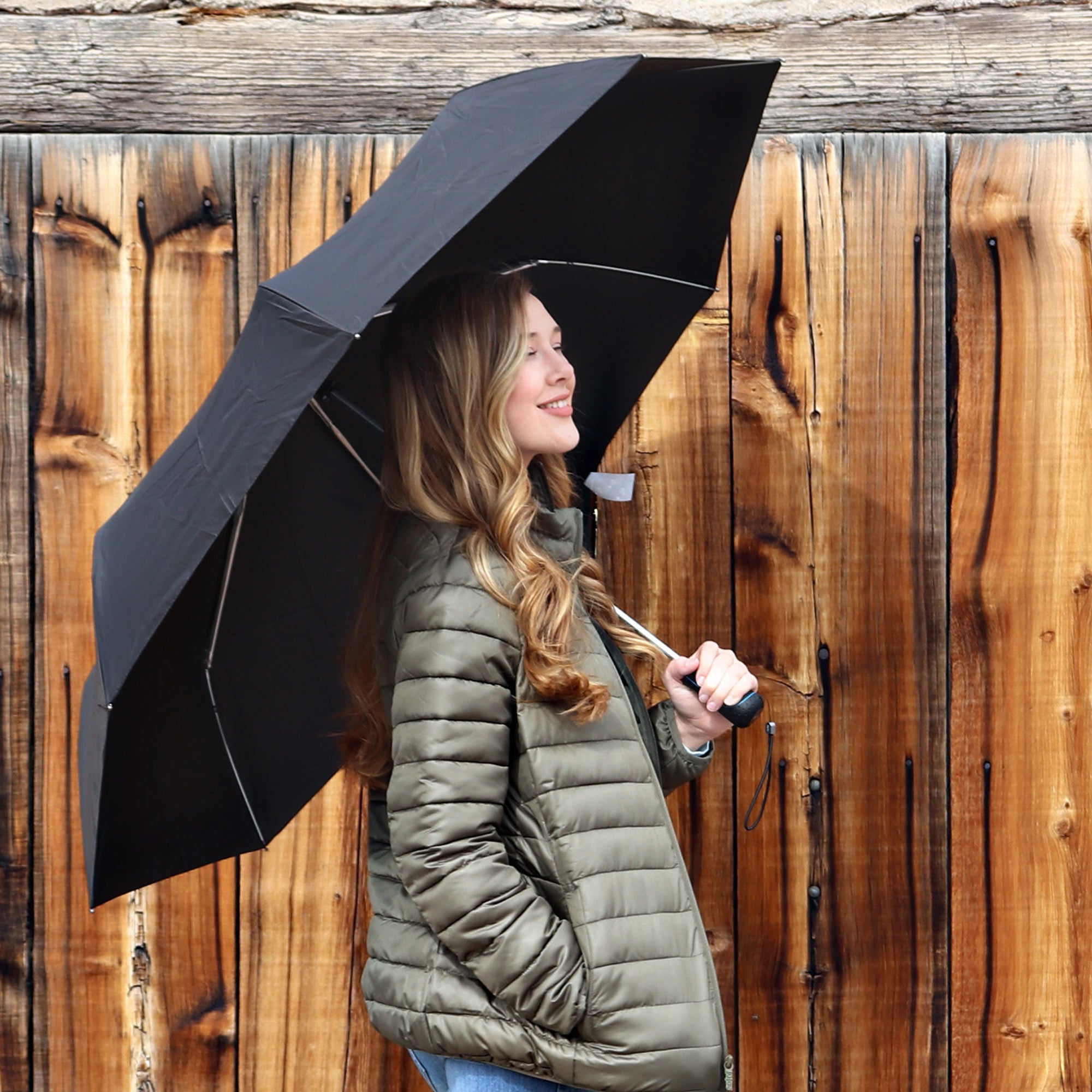 Female model holding a titan umbrella over her head and smiling against a wood fence background
