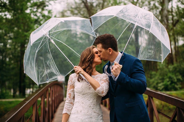 Beautiful couple on their wedding day kissing underneath two bubble umbrellas