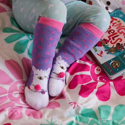 Kid's 2-Pack Novelty Toastie™ Slipper Socks in Llama On Model With Book