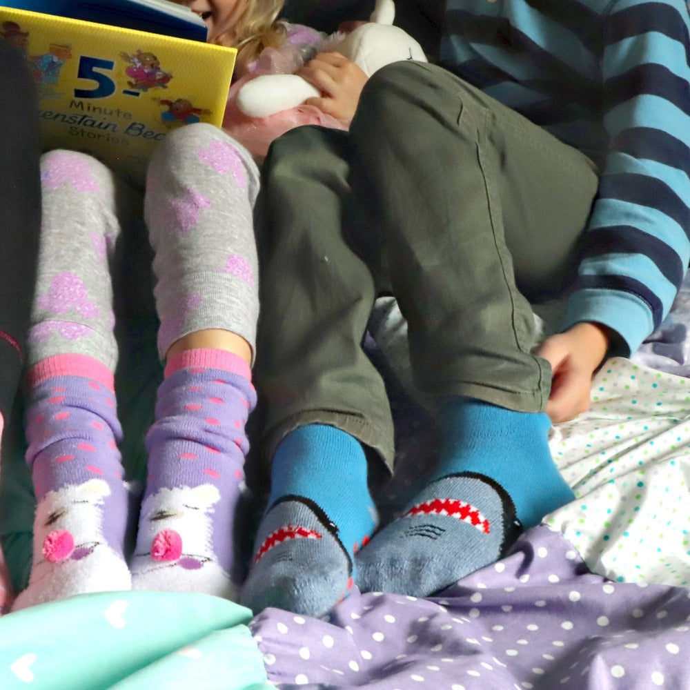 Kid's 2-Pack Novelty Toastie™ Slipper Socks in Sharks and Llama On Models Reading A Book