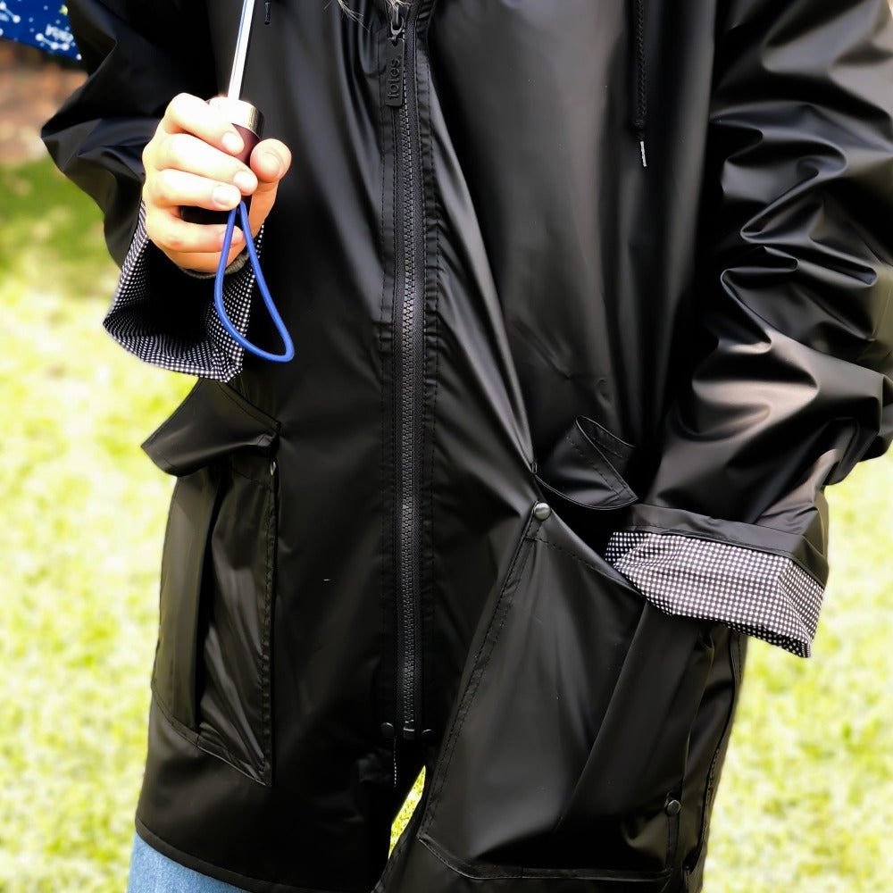 Woman wearing Lined Rain Slicker in black outside holding umbrella