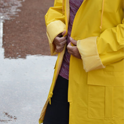 Woman wearing Lined Rain Slicker in yellow outside in rain