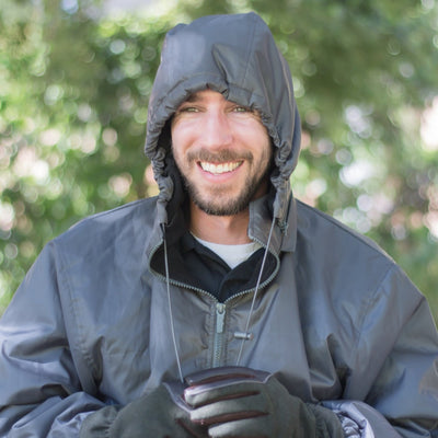 Smiling man wearing Men's Three Season Storm Jacket in gunmetal outside with hood up