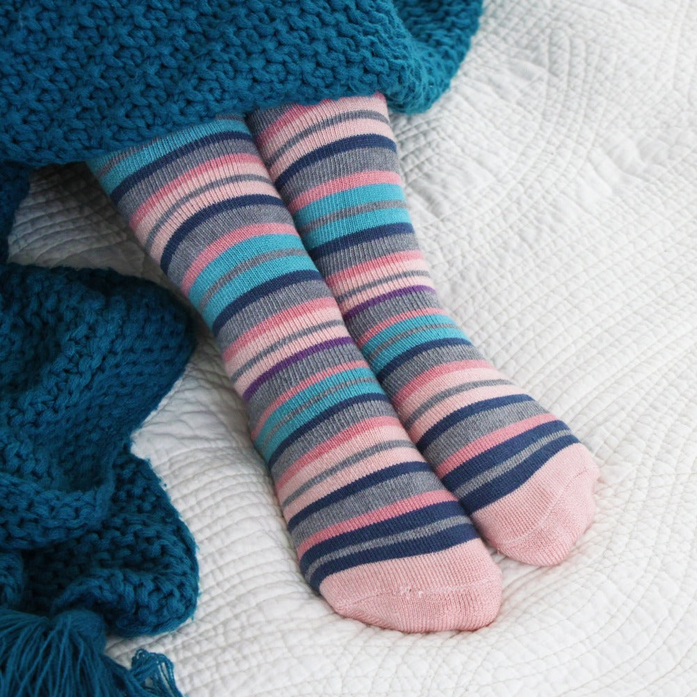 Woman wearing Women's 2-Pack Toastie™ Slipper Socks on white bedspread in blue cozy knit blanket