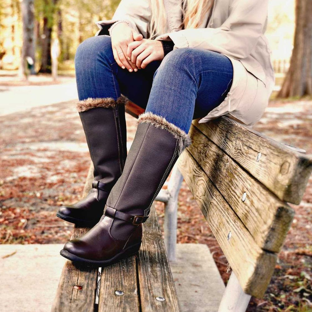 Women's Maryliza Tall Winter Boots in Brown On Model Wearing Rain Slicker On A Park Bench