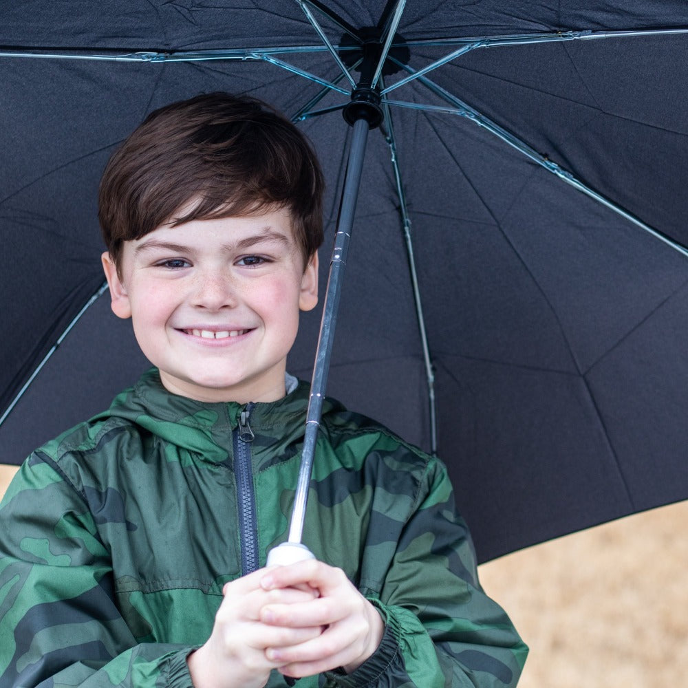 Boy holding Auto Open Close Umbrella in black outside front view