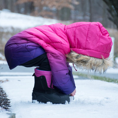 Little girl wearing Girl's Nora Winter Boots outside playing in snow