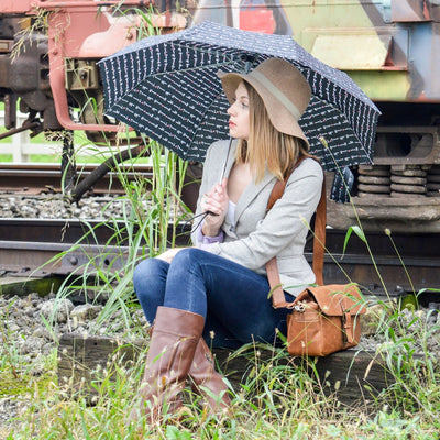 Woman holding Limited-Edition Auto Open Umbrella in love letter outside sitting on train tracks