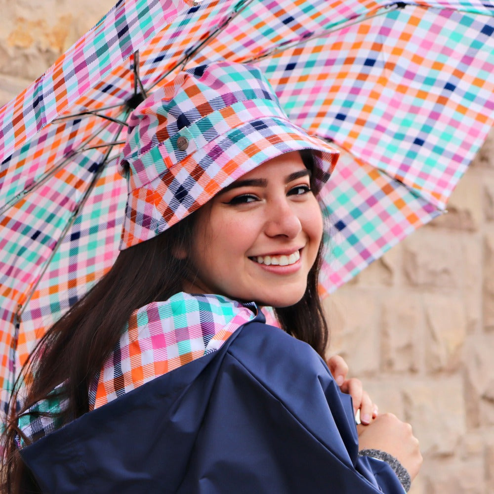 Woman holding Limited-Edition Auto Open Umbrella in rainbow gingham outside on brick wall
