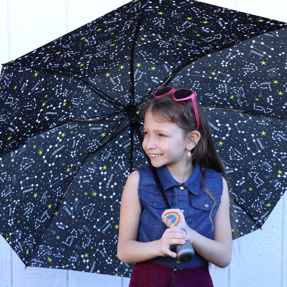 Young kid holding InBrella Reverse Close Folding Umbrella in zodiac black front view