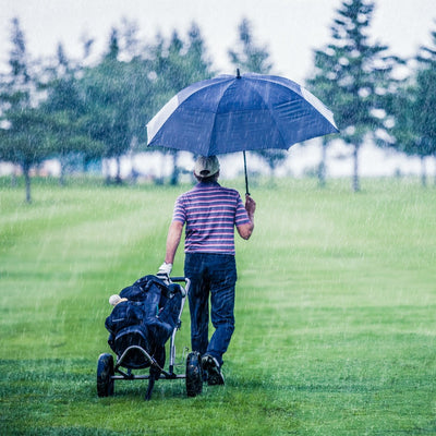 Man golfing holding Totessport Auto Open Golf Stick Vented Canopy Umbrella in black in the rain on the course