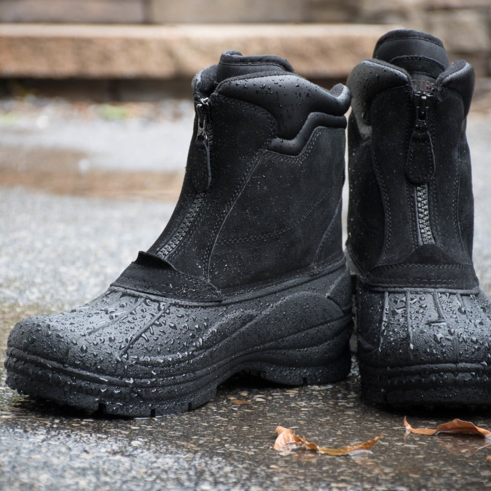 Men's Glacier Winter Boots in black sitting on pavement in the rain