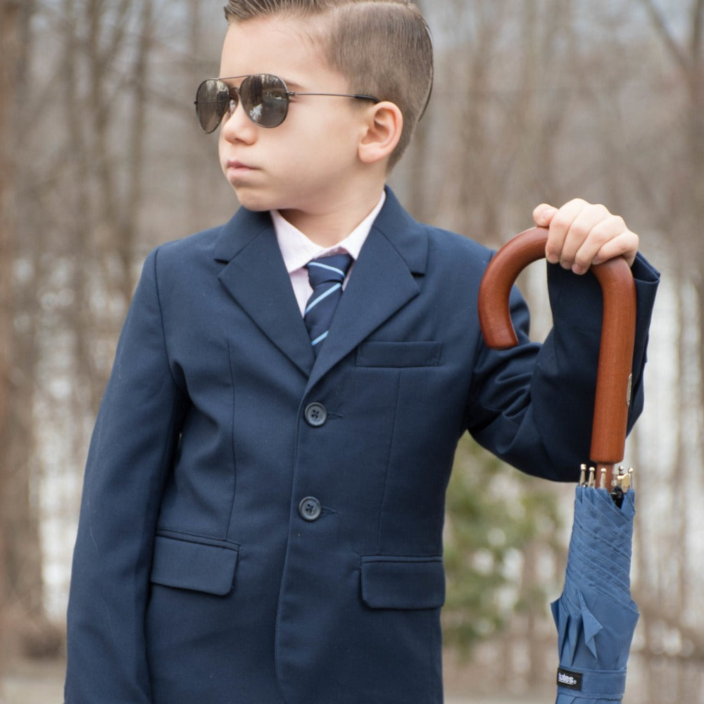 Little boy holding the Blue Line Auto Wooden Stick Umbrella wearing a tux and sunglasses outside frontal view