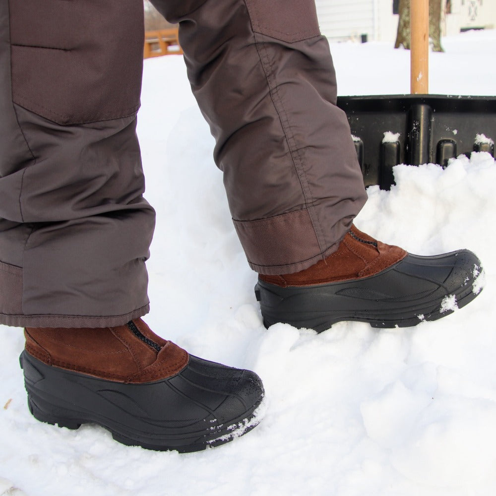 Man wearing Men's Glacier Winter Boots in brown shoveling snow front view