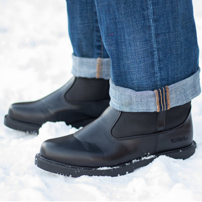 Man wearing Men's Stadium Winter Boots in snow with rolled blue jeans side view