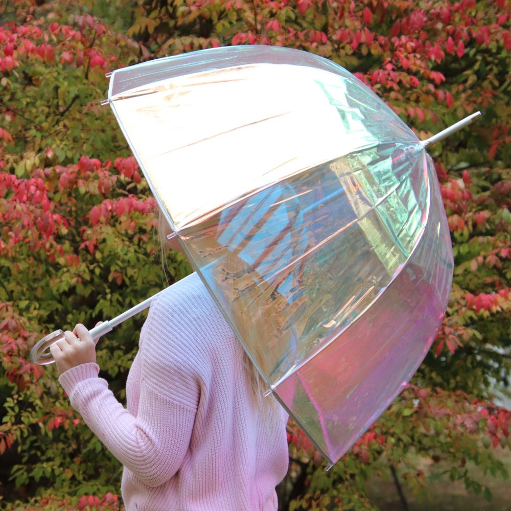 Woman holding Signature Clear Bubble Umbrella in Iridescent in front of fall colored leaves back side view