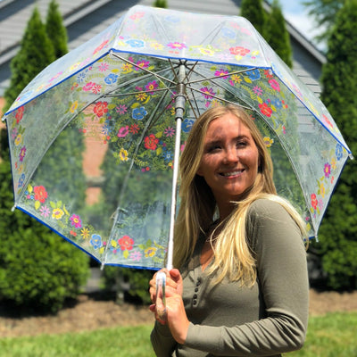 Woman holding Signature Auto Open Bubble Umbrella in embroidered floral outside in the sun