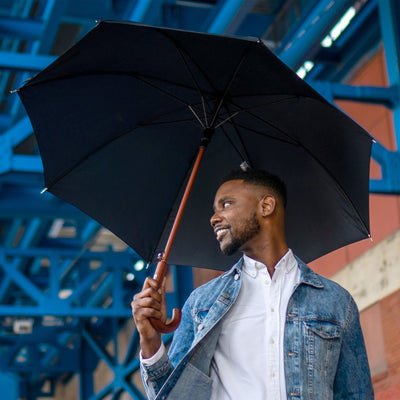 Male model holding black stick umbrella under city scaffolding