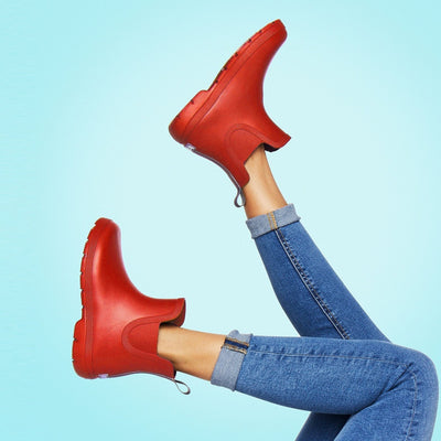 Cirrus™ Women's Chelsea Ankle Rain Boots in Red On Model Against Blue Background