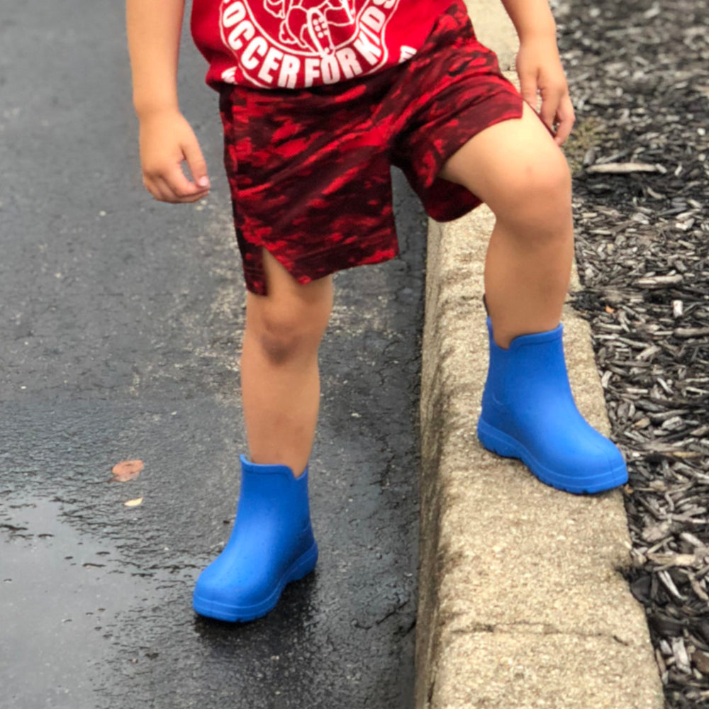 Cirrus™ Toddler's Chelsea Ankle Rain Boot in Regatta on little boy outside with his foot up on a cement curb