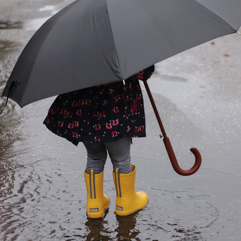 Cirrus™ Toddler's Charley Tall Rain Boot in School Bus On Model with Umbrella in the Rain