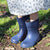 Cirrus™ Toddler's Charley Tall Rain Boot in Navy Blue on model playing in the mud