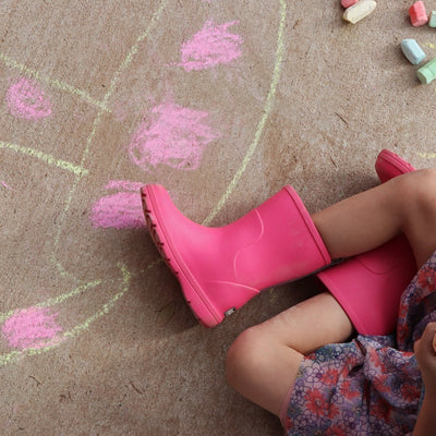 Cirrus™ Kid's Charley Tall Rain Boot in Very Berry On Model Playing with Sidewalk Chalk
